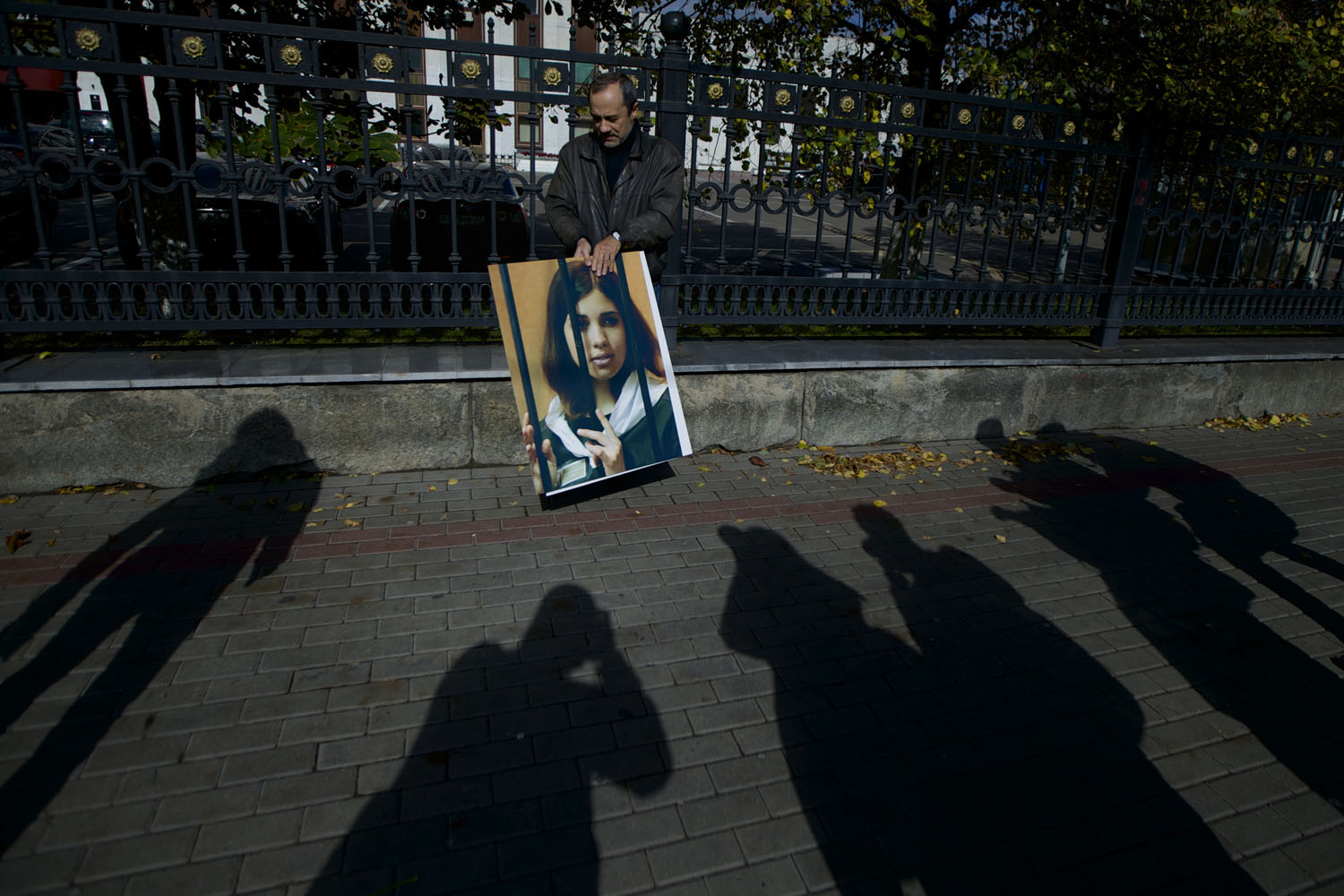 Sept. 25, 2013. Russian journalist Alexander Podrabinek holds a portrait of jailed Pussy Riot punk group member Nadezhda Tolokonnikova, with shadows of reporters in front, during a protest outside of the Federal Prison Administration headquarter in Moscow.