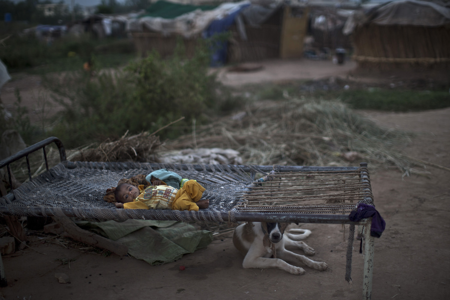 Sept. 25, 2013. A Pakistani child lies in a bed outside his family's makeshift home in a slum in Islamabad, Pakistan.