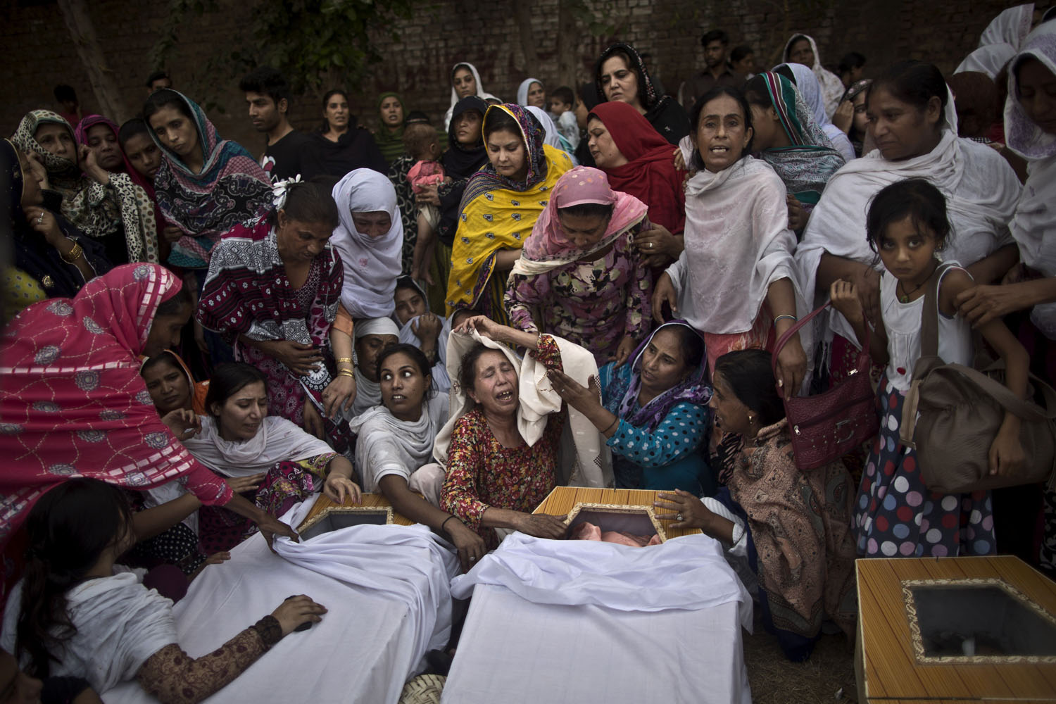Sept. 22, 2013. Pakistani women grieve over the coffins of their relatives, who were killed in a suicide attack on a church in Peshawar, Pakistan.