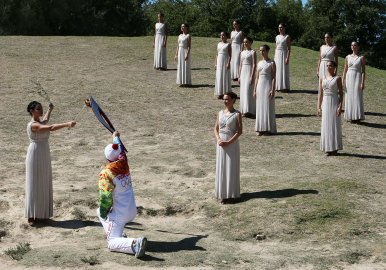 Actress Ino Menegaki as high priestess, left, passes the Olympic Flame to the first torch runner - Greek champion skier Giannis Antoniou - during the final dress rehearsal at Ancient Olympia, in west southern Greece.