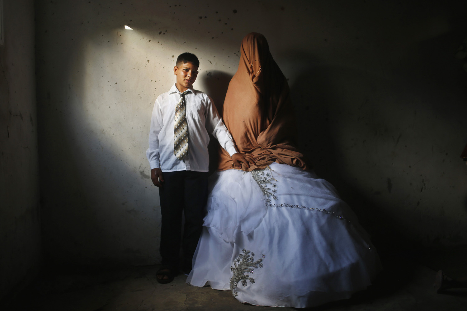 Sept. 24, 2013. Young Palestinian groom Ahmed Soboh, 15, and his bride Tala, 14, stand inside Tala's house which was damaged during an Israeli strike in 2009, during their wedding party in the town of Beit Lahiya, near the border between Israeli and northern Gaza Strip.