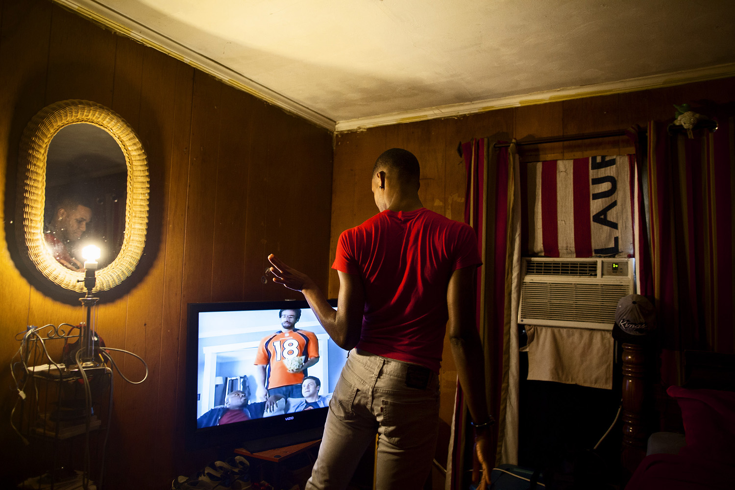 Adrian watches a TV commercial in his bedroom in his mother's house. Several of the members of the line live at home with relatives. Among their ranks, a number have faced considerable difficulty when dealing with family members' reactions to their orientation.
