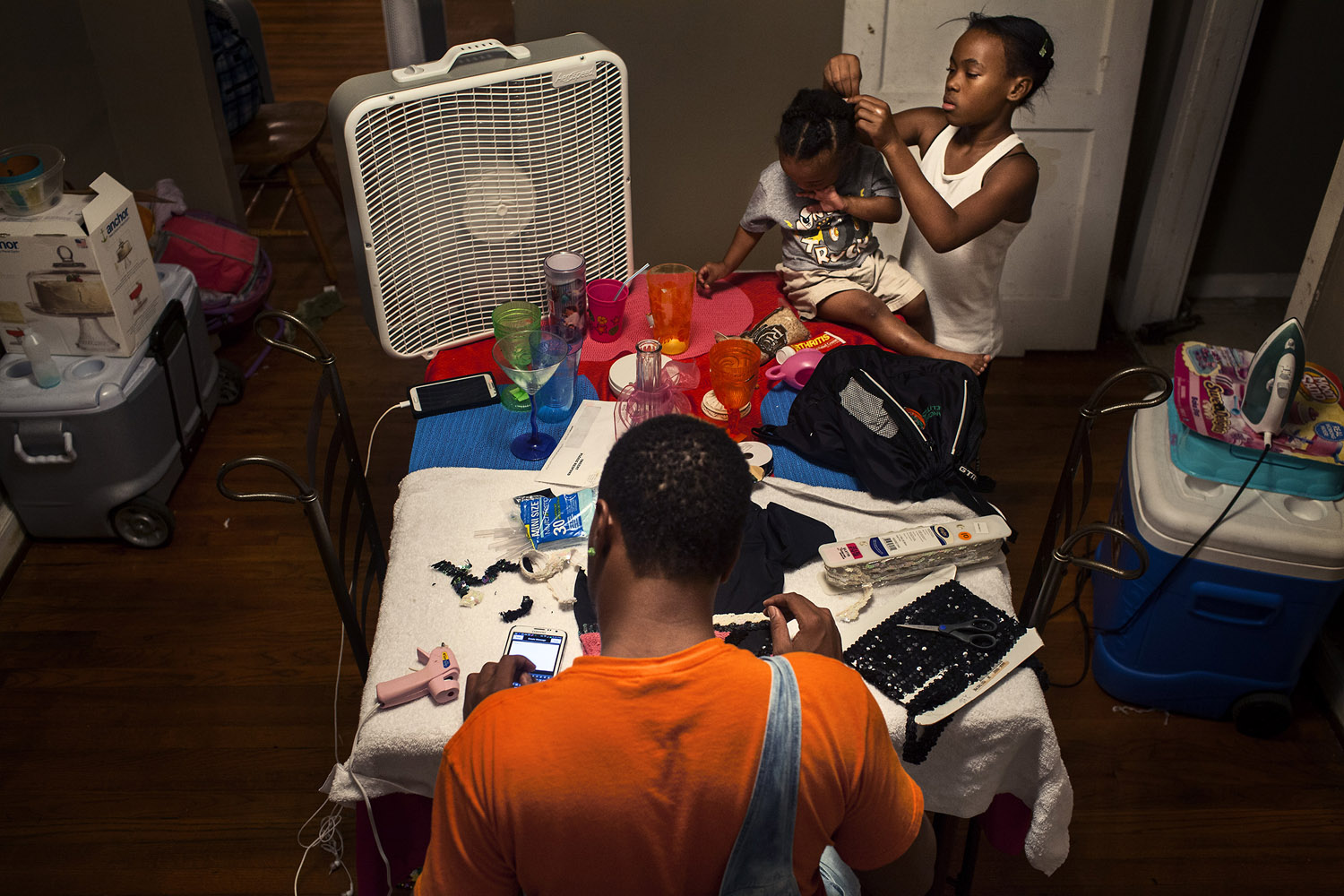 Kentrell sits in his mother's dining room creating a new performance outfit with a standard leotard, sequins, a hot glue gun and a pair of scissors. He designs most of the costumes for the Prancing Elites, utilizing basic craft materials and his own creativity. His niece and nephew watch as he works. Kentrell's niece, who is 12, also practices J-Sette dance.