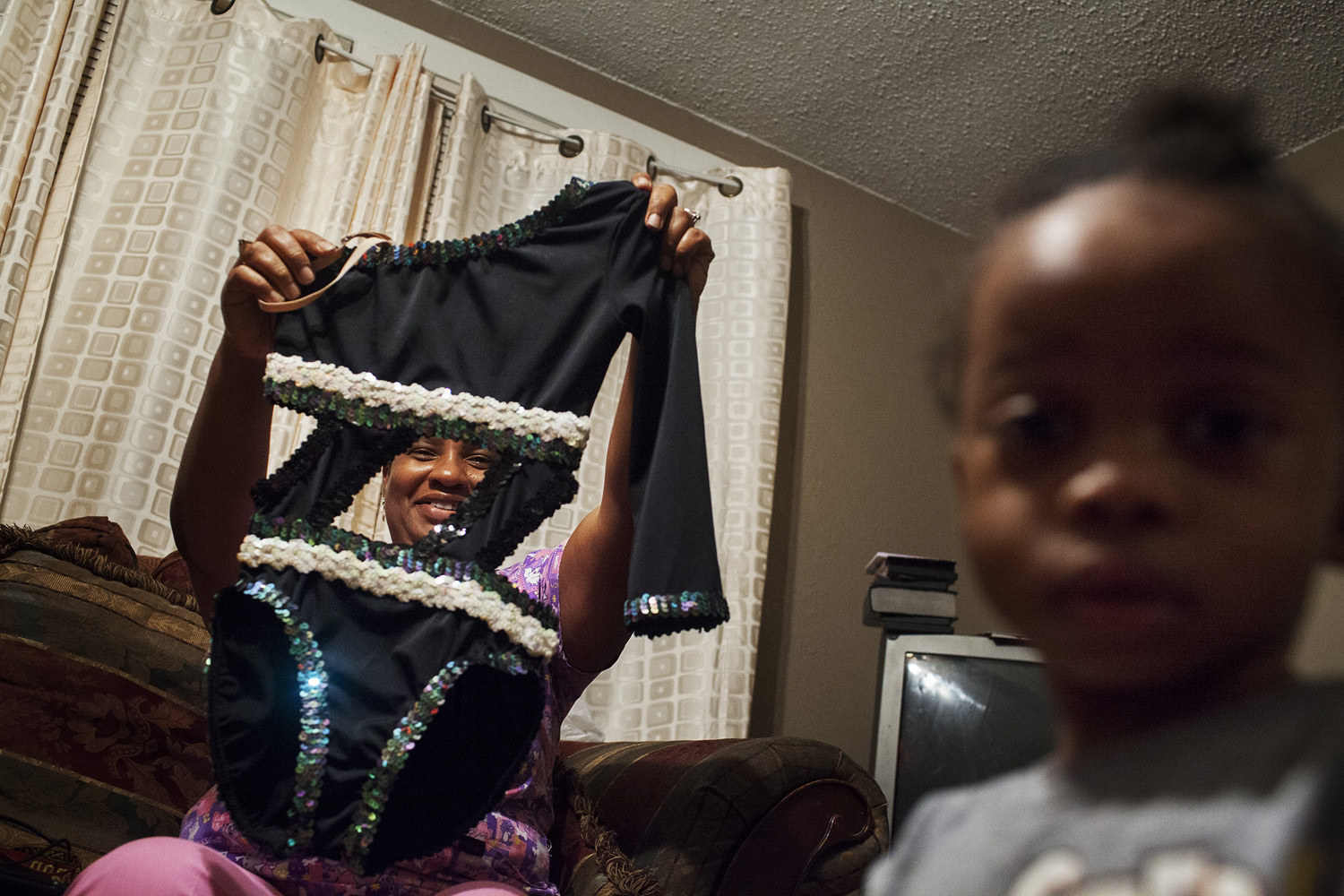 Kentrell's mother holds up a leotard he designed and customized, admiring his craftsmansip.