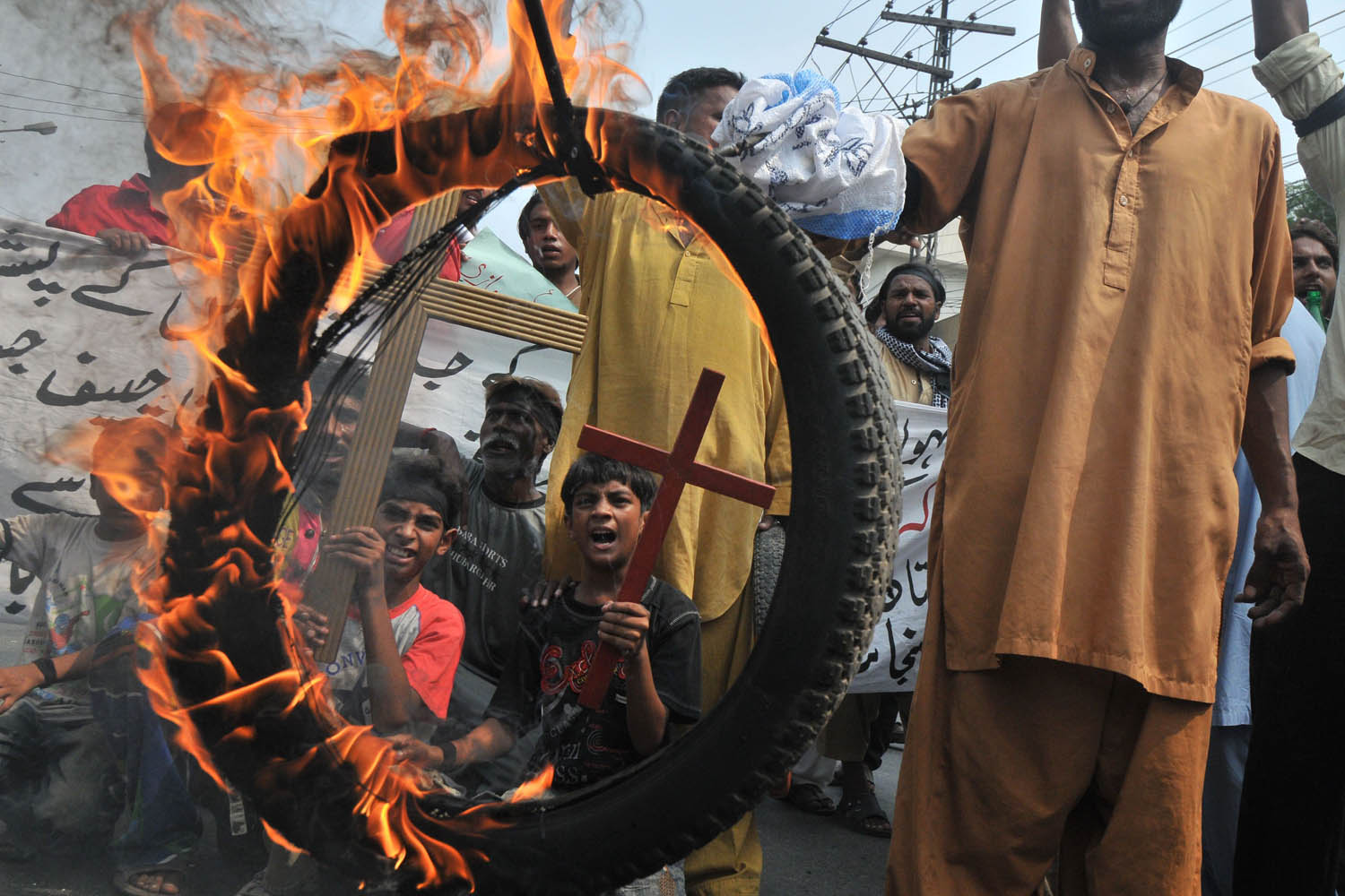 Sept. 23, 2013. Pakistani Christians hold a burning tire as they stage a protest in Lahore against the suicide bombing of a church in Peshawar.