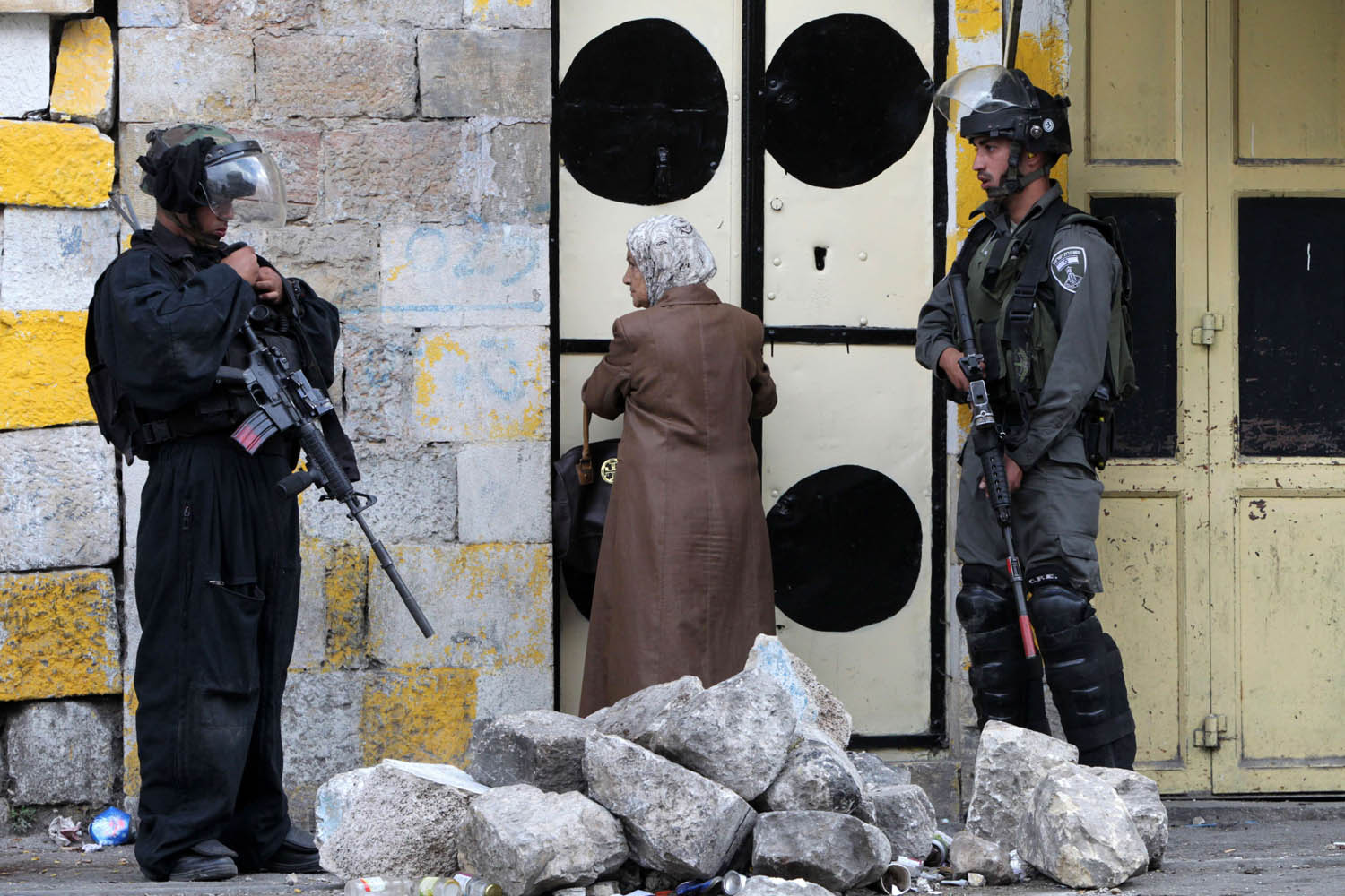 Sept. 24, 2013. A Palestinian woman looks at Israeli security forces standing outside her door as they monitor the streets during clashes with Palestinian stone throwers in the divided West Bank city of Hebron, near the Jewish settlements of Beit Hadassa and Tal Romeda.