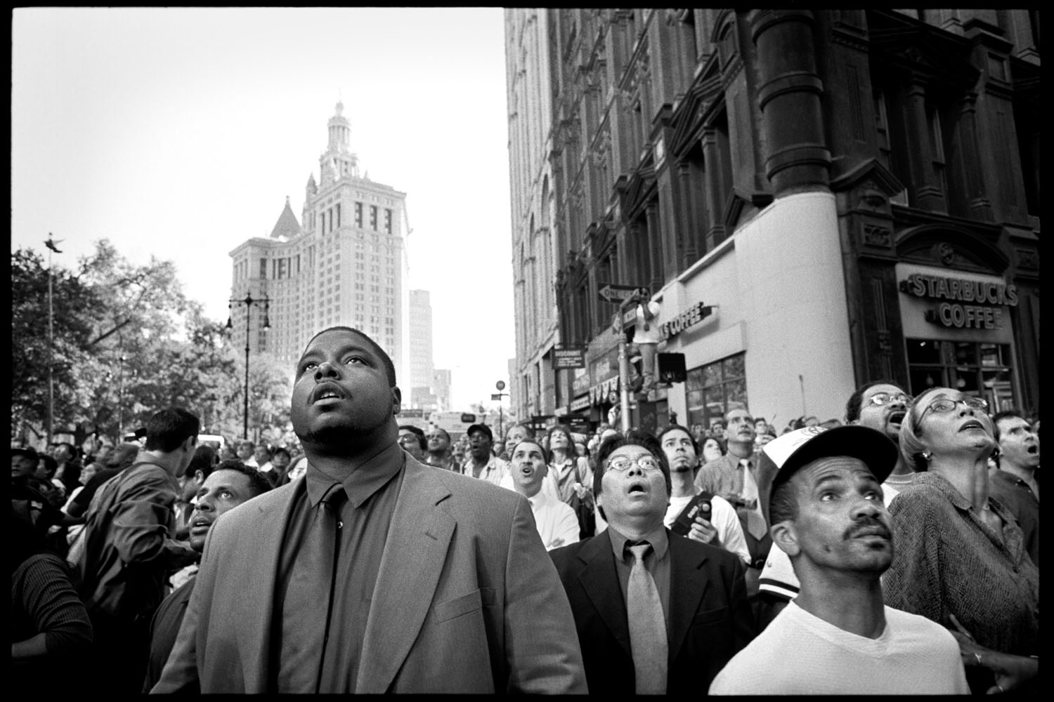 A crowd of stunned New Yorkers witness the collapse of the South Tower of the World Trade Center at 9:59am on September 11, 2001. The photographer used social media to identify Benjamin Tabile, the man wearing  glasses in the center of the frame.