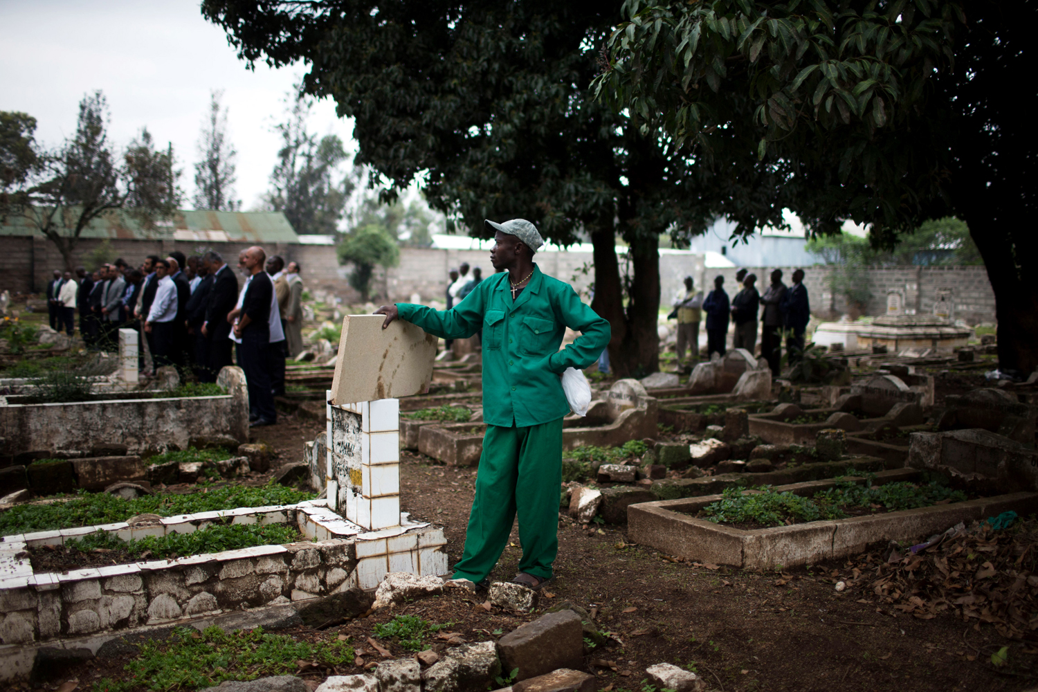 Sept. 25, 2013 A cemetery worker looks on as friends and relatives mourn during a funeral service for Selima Merali (41) and her daughter Nuriana Merali (15), who were killed in the attack by gunmen at the Westgate Shopping Centre, in Nairobi, Kenya.