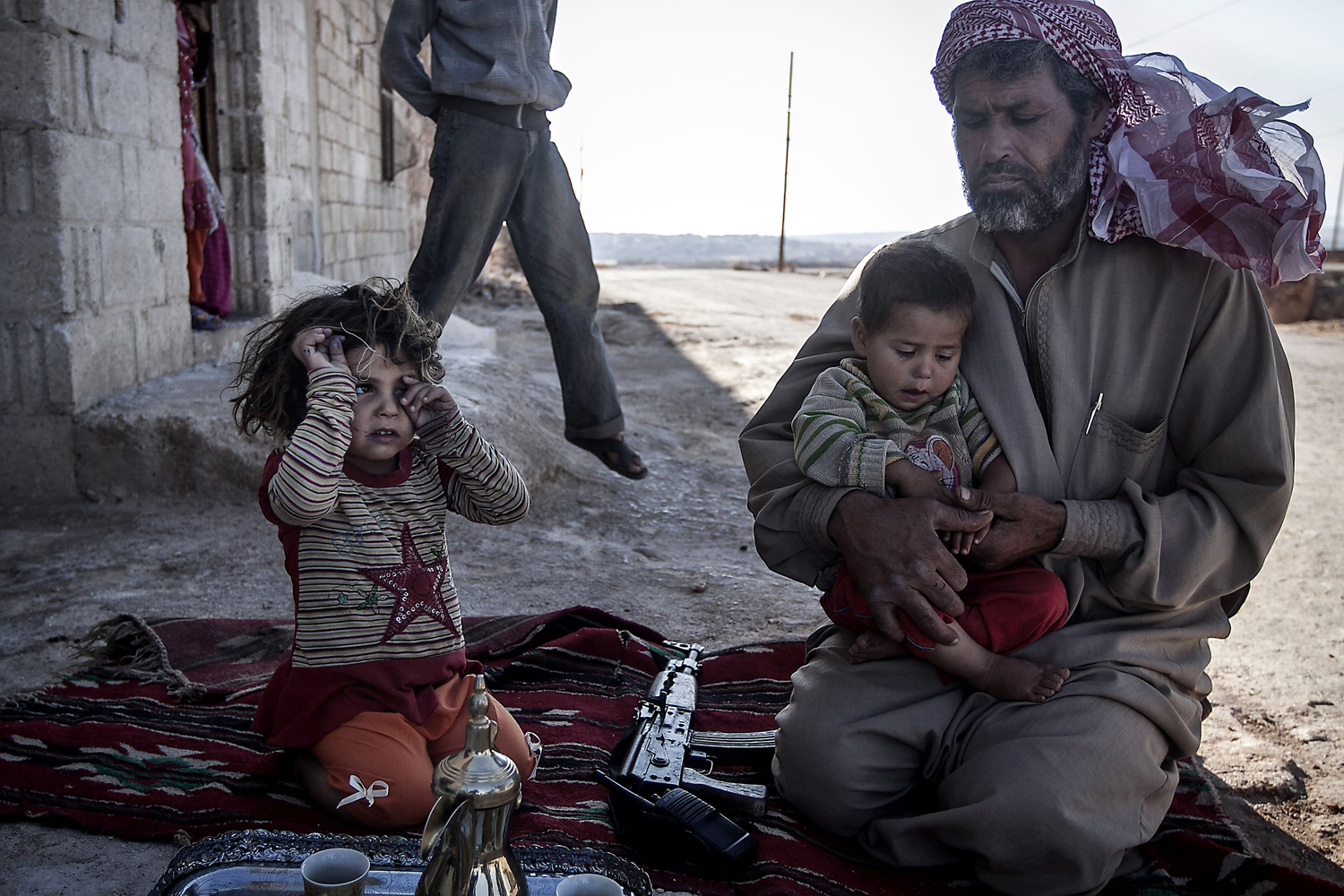 Sept. 25, 2013. A Free Syrian Army fighter holds his son outside their home in Habit village, the Syrian central province of Hama.