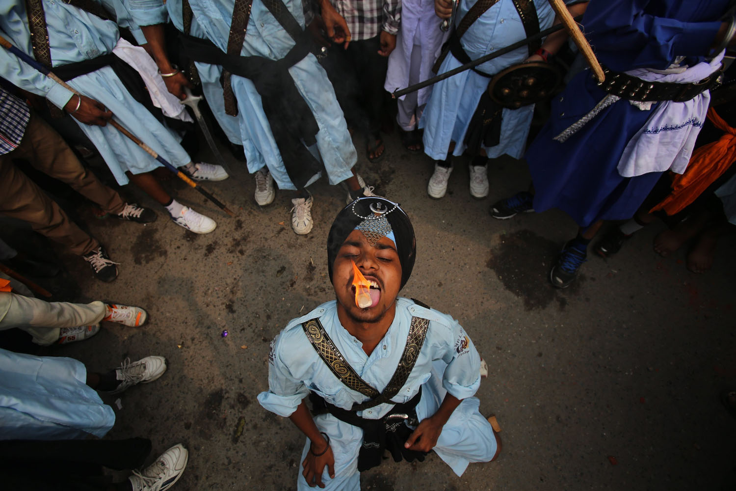 Oct. 8, 2013. A Sikh man puts a burning camphor on his tongue as he performs 'Gatka', an ancient form of Sikh martial arts during a religious procession in Amritsar, India.