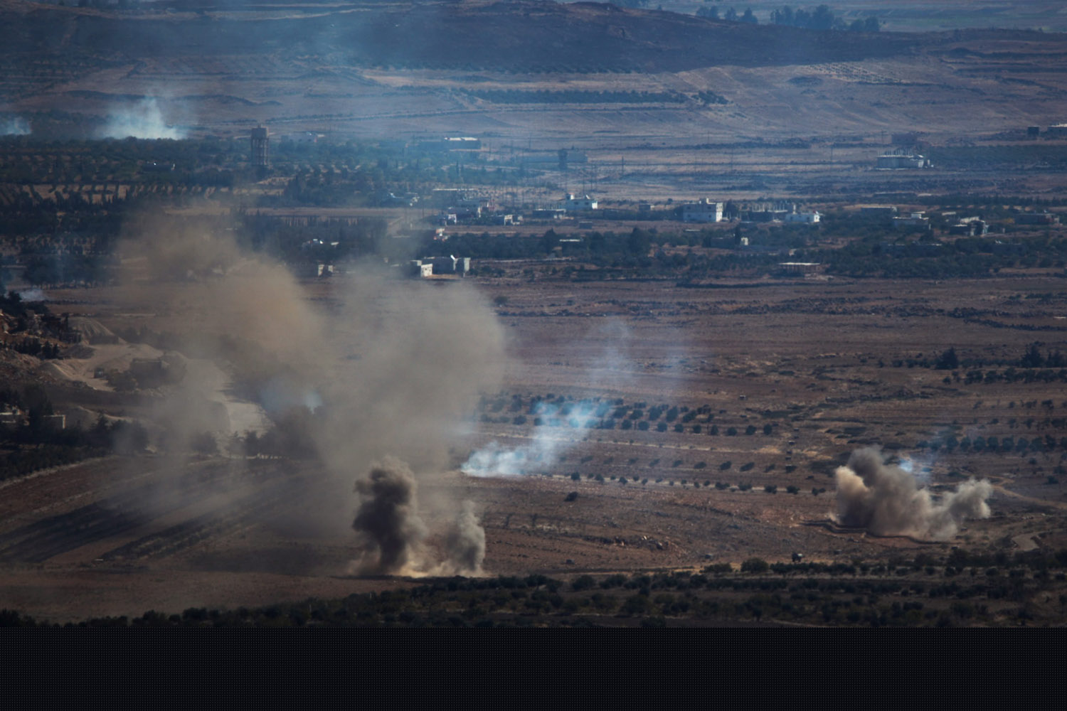 Oct. 8, 2013. Israelis watch smoke rising due to a fire caused by mortars near the village of Afania on the Syrian side of the border with Israel in the Golan Heights.