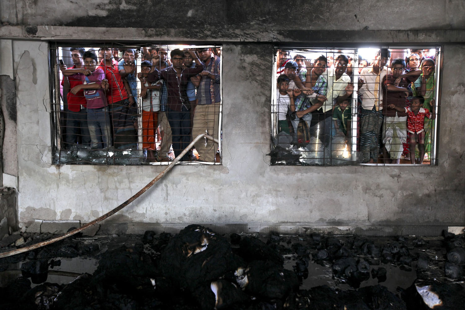 Oct. 9, 2013. People watch the rescue operation from outside the factory after a devastating fire at the dyeing section of two-storey Aswad Composite Mills at Maona, Gazipur, Bangladesh.