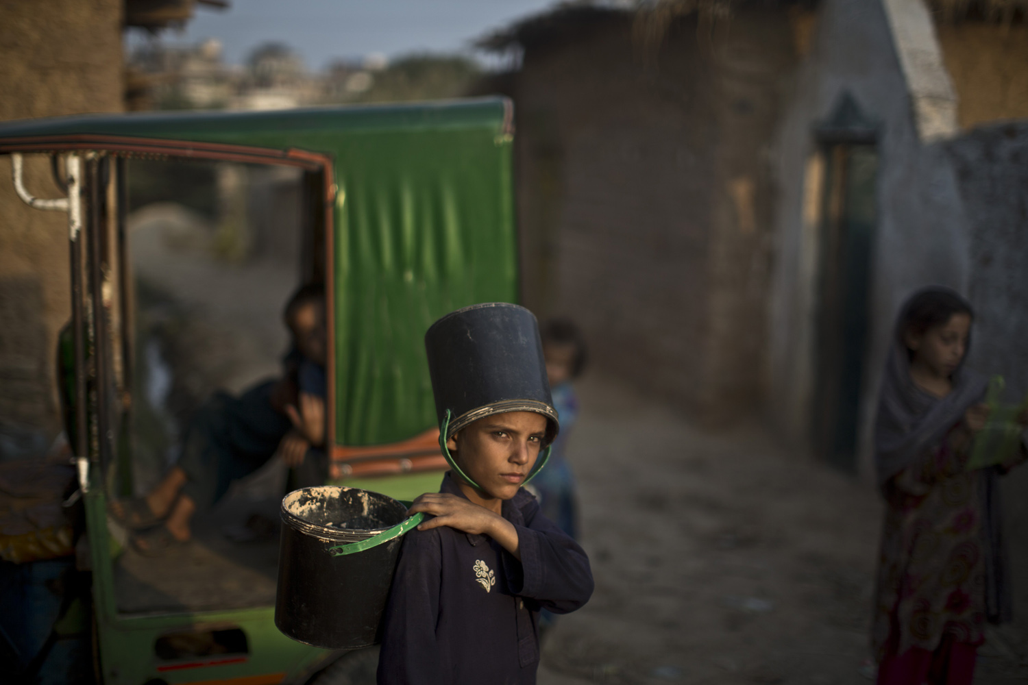 Oct. 7, 2013. An Afghan refugee boy wearing an empty bucket on his head, waits his turn to fetch water from a hand pump in a poor neighborhood on the outskirts of Islamabad, Pakistan.
