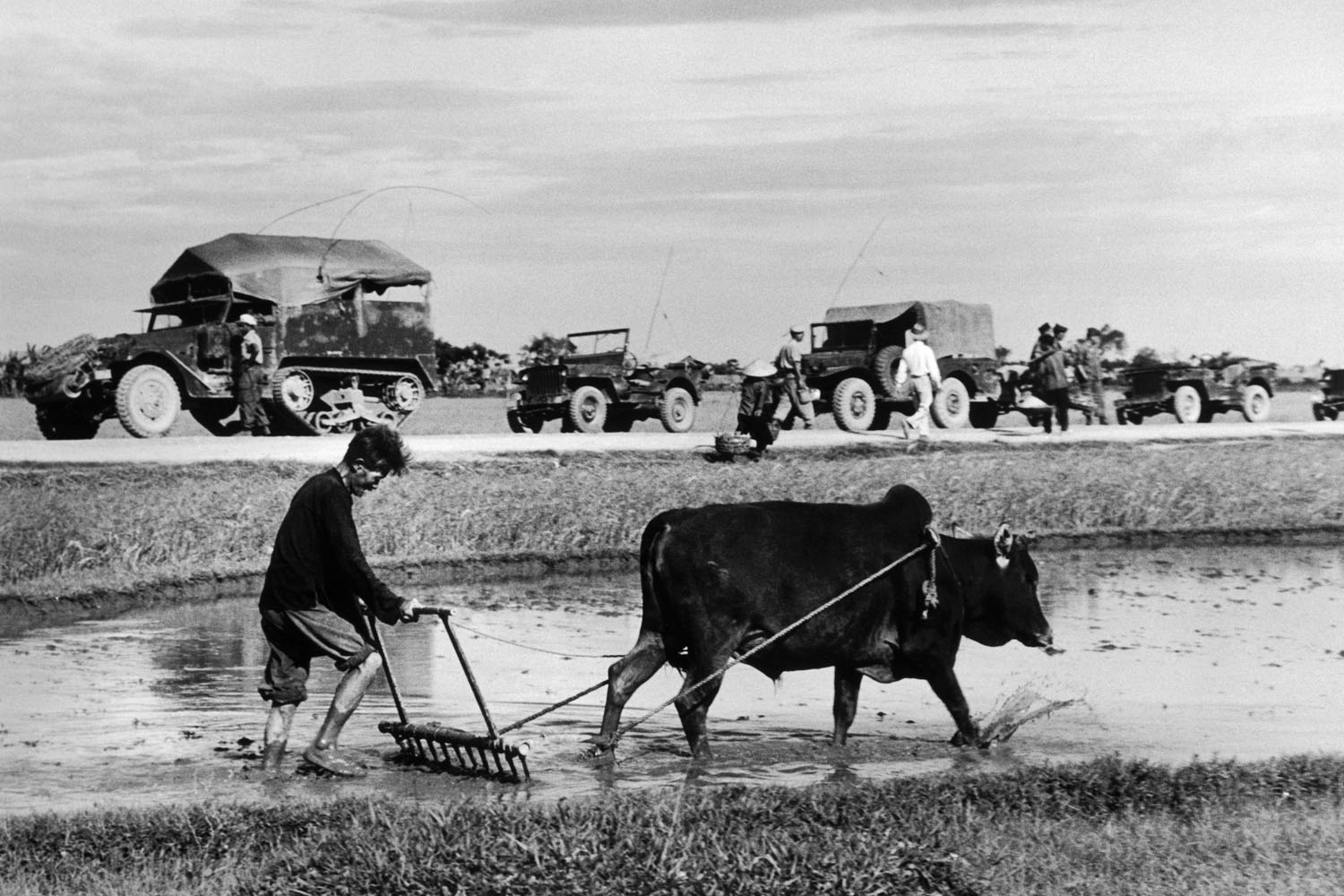 A French military convoy marches past a rice field on its way north towards Doai Tan, Vietnam, May 25, 1954.Robert Capa was killed by a landmine on the afternoon that this photograph is dated while on assignment for LIFE, covering the First Indochina War. The frame was captured on what is likely one of the last rolls of film he ever exposed.