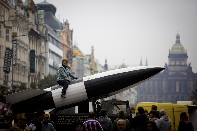 Oct. 7, 2013. A participant dressed as German Chancellor Angela Merkel sits on a large rocket during the 'Klassenkampf statt Weltkrieg' (Class Struggle Instead of World War), a campaign supported by Deutsche Kommunistische Partei (DKP), at the Wenceslas square in Prague.