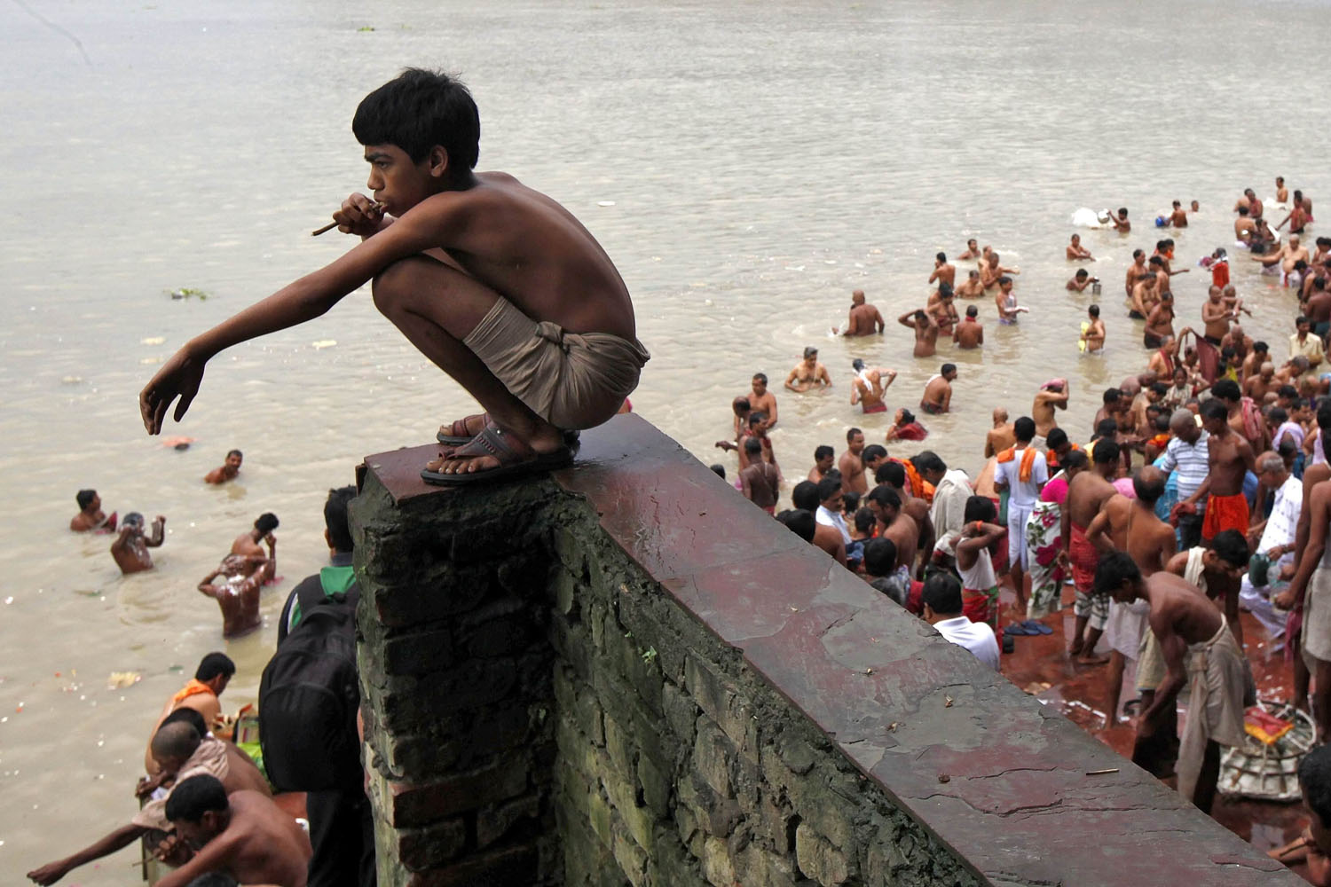 Oct. 4, 2013. A Hindu boy brushes his teeth with a neem twig as others take a dip on the banks of the Ganges river on the holy day of  Mahalaya  in Kolkata, India.