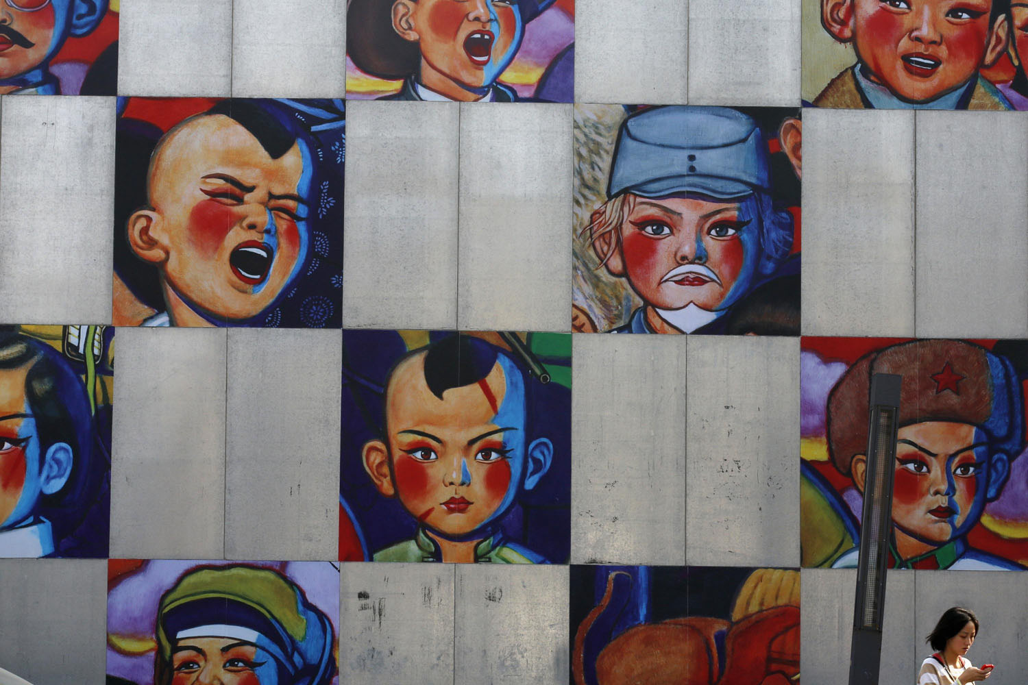 Oct. 8, 2013. A woman walks past a gallery's wall bearing the paintings by Song Changqing during the 2013 Beijing 798 Art Festival at the 798 Art Zone in Beijing.
