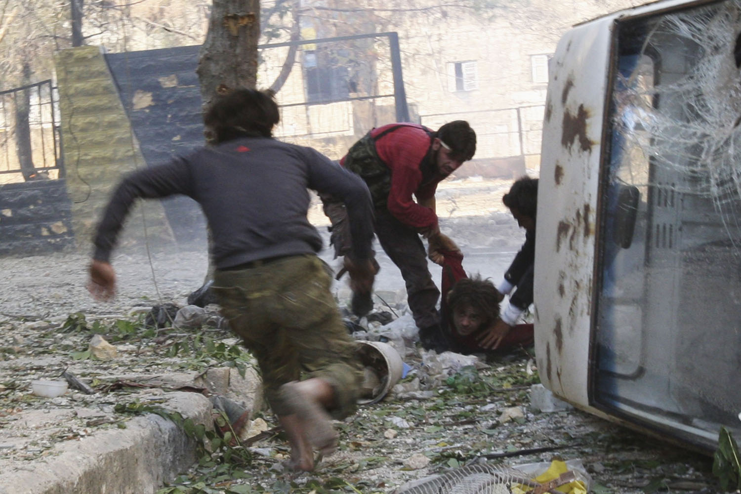 Oct. 9, 2013. Free Syrian Army fighters rush to help their fellow fighter after he was shot by a sniper loyal to Syria's President Bashar al-Assad in Aleppo's Salaheddine neighborhood.