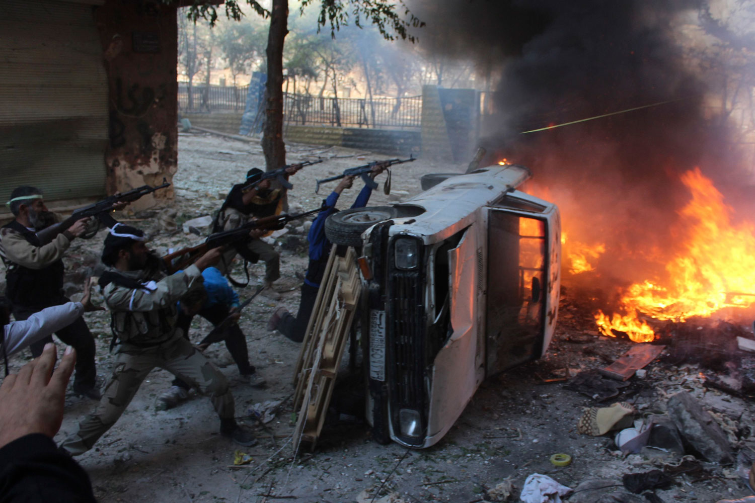 Oct. 9, 2013. Free Syrian Army fighters take position behind a damaged car as they fire weapons on forces loyal to President Bashar Assad in Aleppo's Salaheddine neighborhood. Tires and other objects are set on fire to provide cover from the snipers.