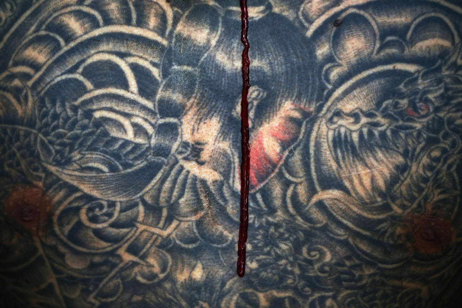 Oct. 10, 2013. Blood trickles down the tattooed torso of a devotee of the Chinese Bang Neow Shrine as he is pierced before the beginning of a street procession during the annual vegetarian festival in Phuket, Thailand.