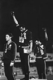 Tommie Smith (center) and John Carlos (right) raise black-gloved fists during the American national anthem; Australian silver medalist Peter Norman, who supported their protest, is at left.