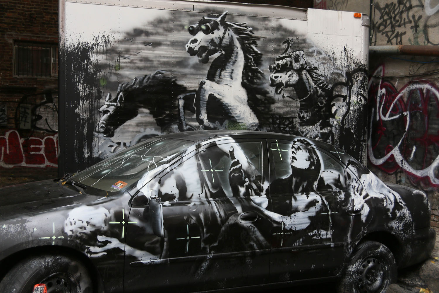 Oct. 9, 2013. The latest Banksy, featuring a man in the crosshairs peering up at three galloping horse in night vision goggles, appears in Lower Manhattan complete with WikiLeaks audio.