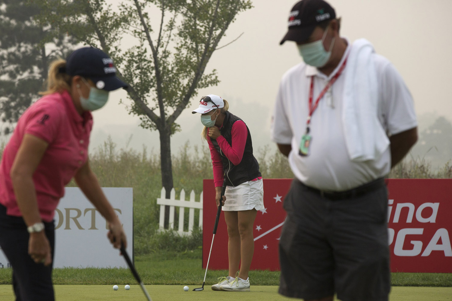Oct. 5, 2013. Golfers wear masks as they practice putting on a hazy morning for the third round of the Reignwood LPGA Classic golf tournament at Pine Valley Golf Club on the outskirts of Beijing.