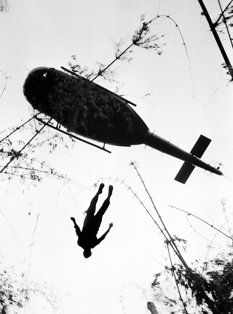 Book. Vietnam: The Real War, by The Associated Press and Abrams. October 1, 2013. Pictured: The body of a U.S. paratrooper killed in action in the jungle near the Cambodian border is lifted up to an evacuation helicopter in War Zone C, May 14, 1966..