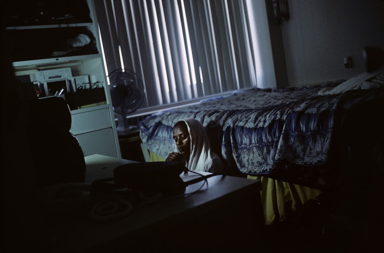 Exhibition. Gabriele Stabile,  Refugee Hotel.  Bronx Documentary Center, Bronx, New York. On view until December 1, 2013. Pictured: Fatuma Obisu Ka-kawa listens to an english course on the stereo in her father's room, in Minneapolis, MN, 2007.