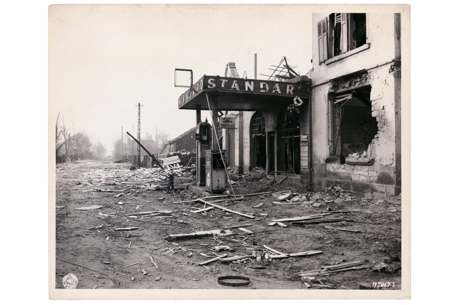 Destruction left in the wake of the battle for Fraulautern, Germany. Reminiscent of home is a Standard Oil gas station