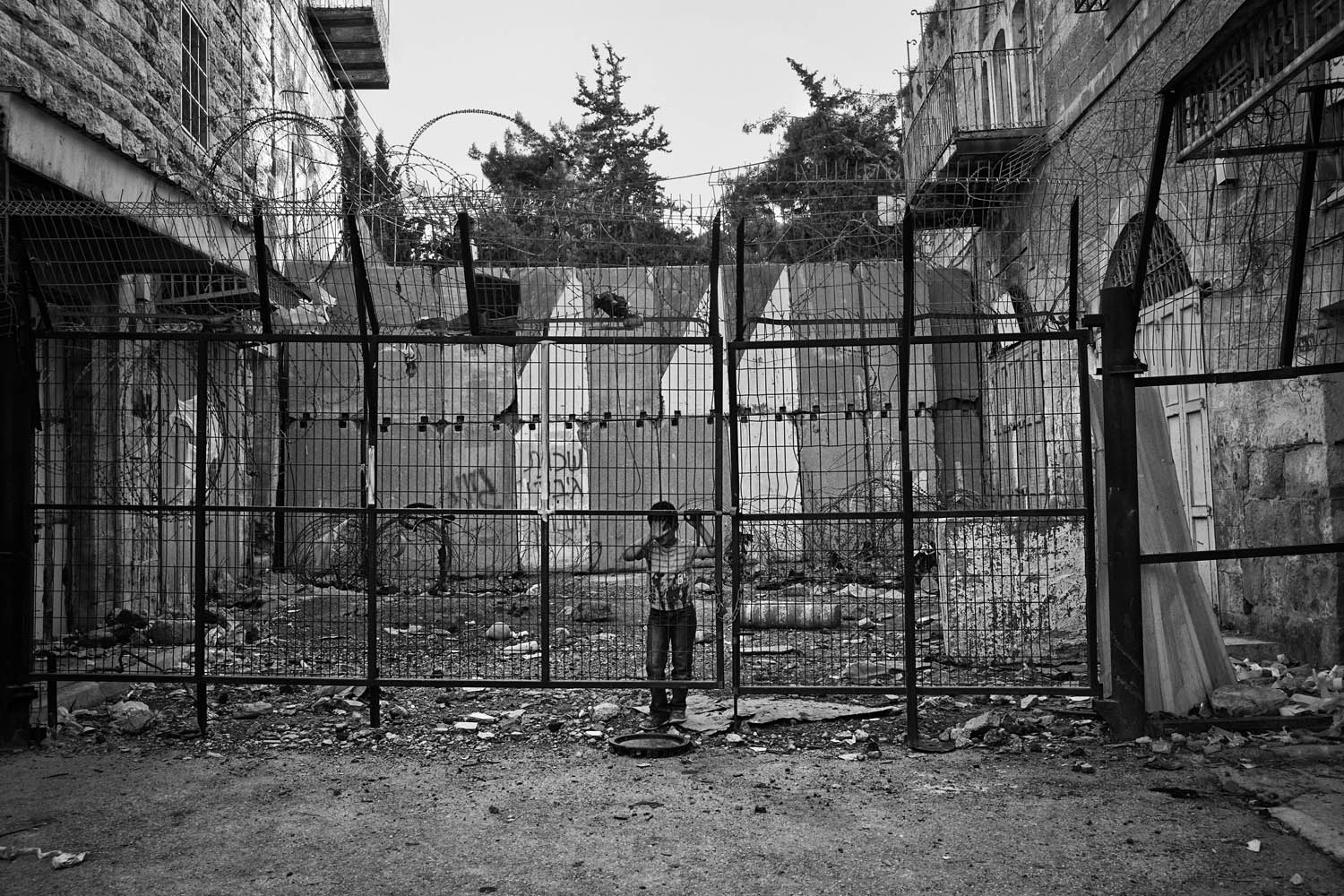 A young boy waits for his friend to play in a closed street of the H2 zone in Hebron, West Bank, April 28, 2013.