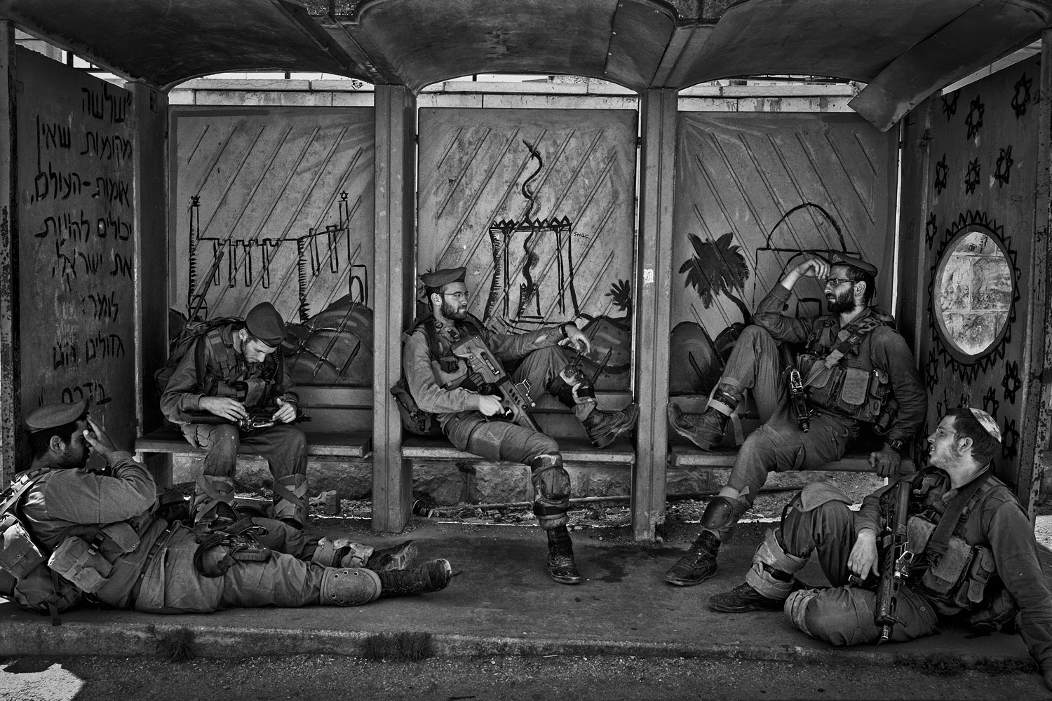 Soldiers from the elite unit  Givati  rest at a bus stop in the settled part of Hebron, West Bank, June 12, 2013.