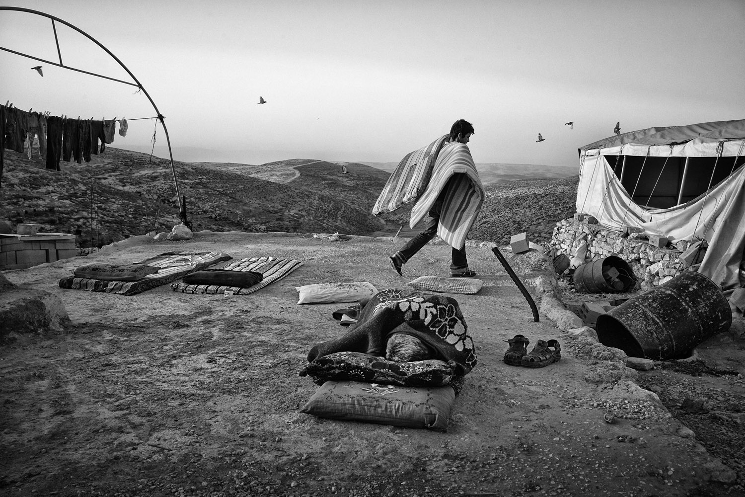 A Palestinian man wakes up in the ruins of his family's West Bank house, destroyed by the Israeli army, in the village of Mufakara in the hills south of Hebron, June 7, 2013.