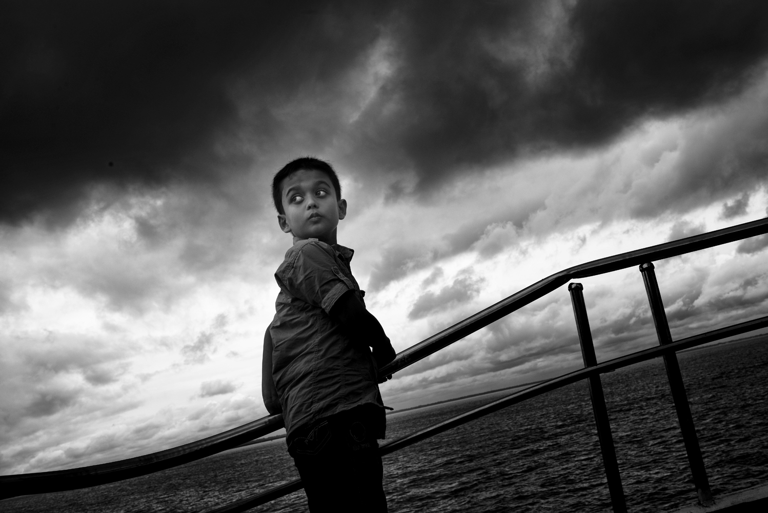 A little boy travels by boat                               from Dhaka to Chandpour on the Buriganga River, Bangladesh.