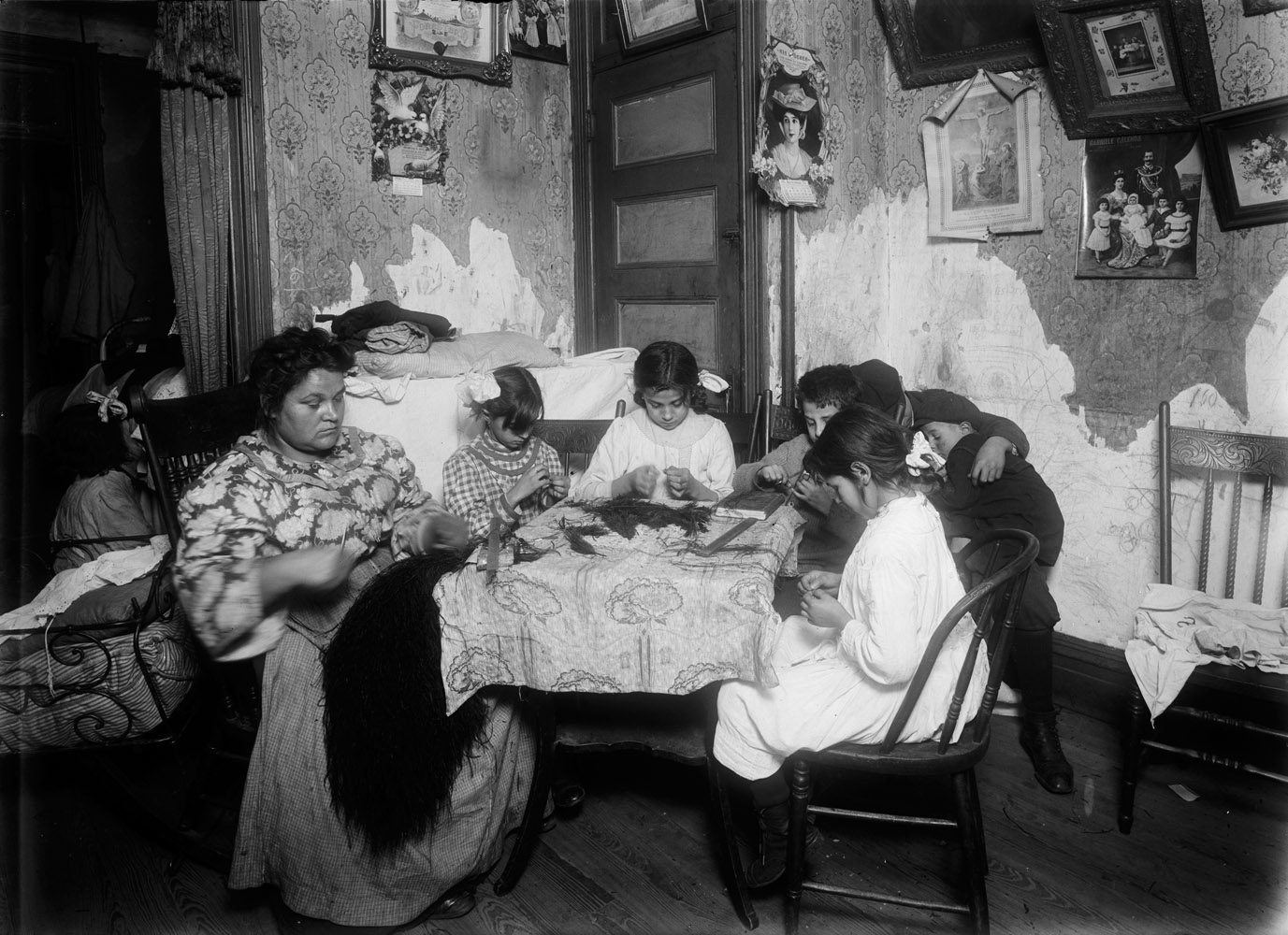 "Mary Mauro and family, working at home for a feather factory, New York City, 1911. 5 P.M. Mrs. Mary Mauro, 309 E. 110th St., 2nd floor. Family work on feathers. Make $2.25 a week. In vacation 2 or 3 times as much. Victoria, 8 yrs. Angelina 10 yrs. (a neighbor). Frorandi 10 yrs. Maggie 11 yrs. All work except two boys against wall. Father is street cleaner and has steady job. Girls work until 7 or 8 P.M. Once Maggie (11 yrs.) worked until 10 P.M.  —Hine's original captionThe photograph is exhibited at the Ellis Island Immigration Museum. ""I went to Ellis Island and found this picture of my father's family. When I saw the photo, it gave me an opportunity to step back in time, and to actually enter the room where they were. I have always felt an appreciation for what I have. Our family has achieved so much since the picture was taken. I feel very proud."" —Daughter of one of the boys in the photograph"