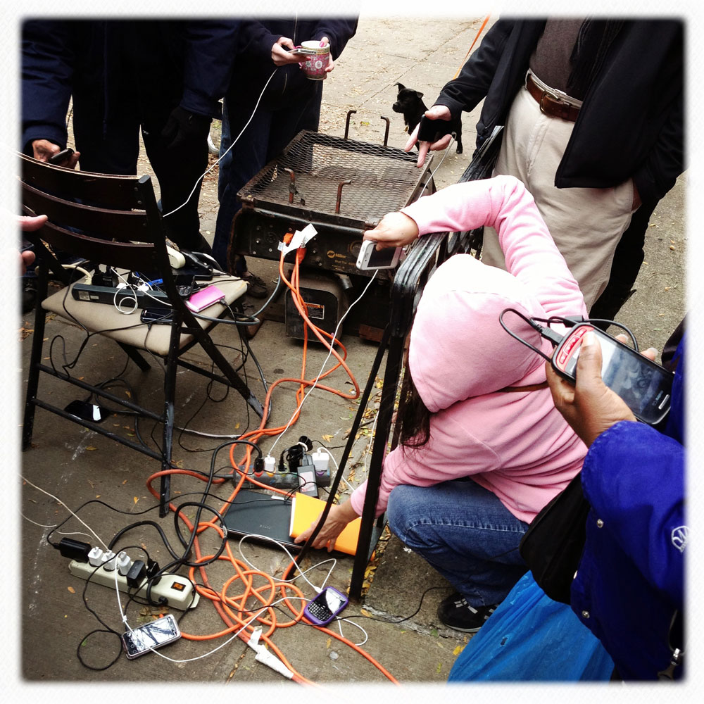 New Yorkers charge their mobile phones with generators provided by Percy's Tavern, located on Avenue A and 13th Street, New York, N.Y., 2012