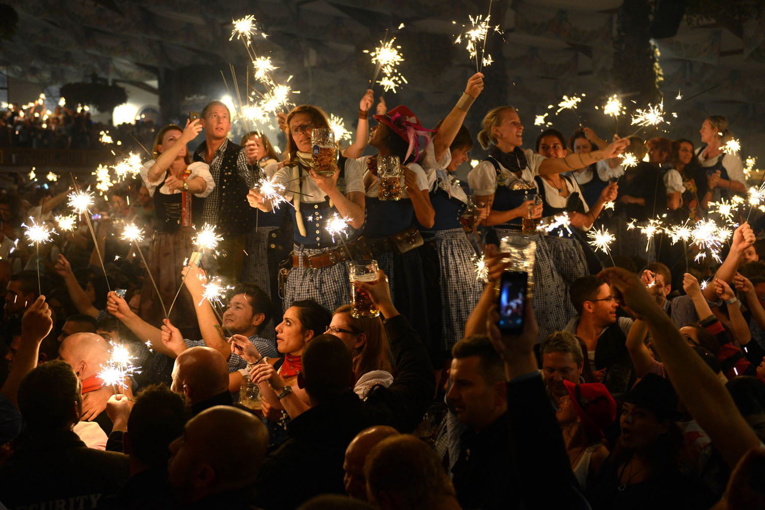 Oct. 6, 2013. Visitors and waitresses celebrate the end of this year's Bavarian Oktoberfest beer festival at the Theresienwiese in Munich.
