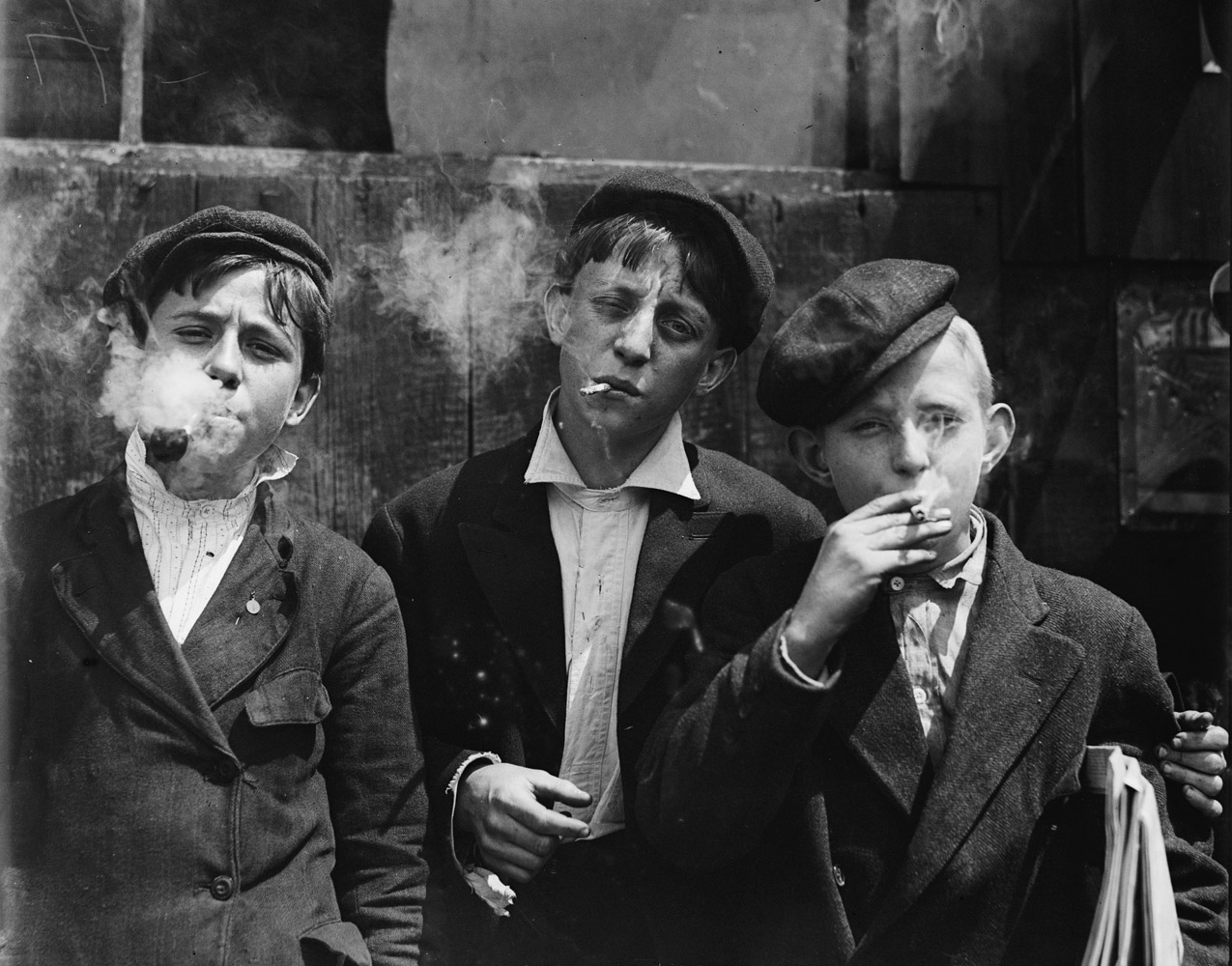 "Raymond Klose (middle), newsboy, 13 years old, St. Louis, Missouri, 1910. 11:00 A.M. Monday, May 9th, 1910. Newsies at Skeeter's Branch, Jefferson near Franklin. They were all smoking.  —Hine's original caption""He was fun, a very funny guy. He always liked to act silly around his nieces and nephews. He had the show dogs, and that was interesting to hear about. He always had at least one at home. They were always Airedales."" —Niece of Raymond Klose"