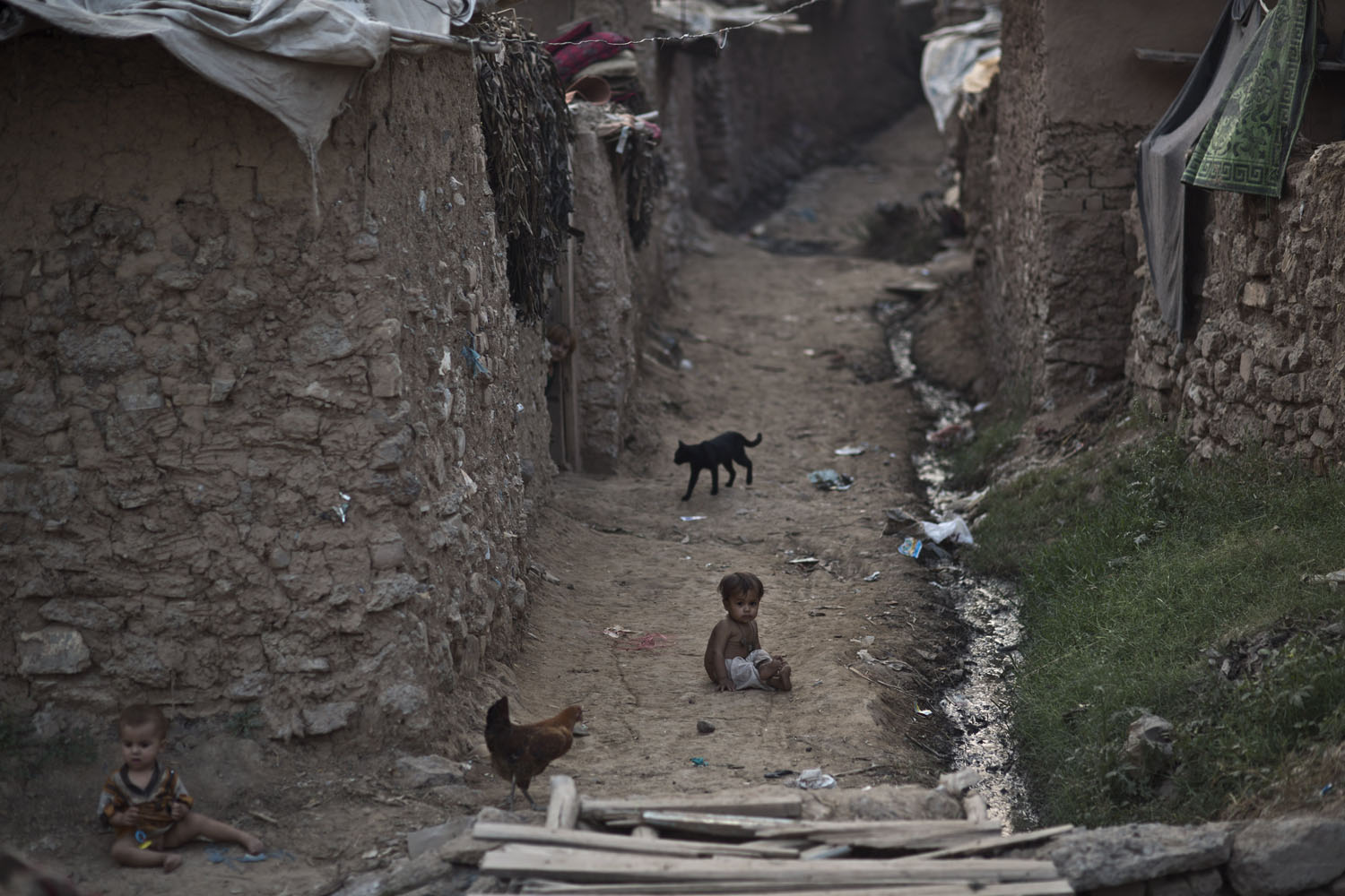 Oct. 10, 2013. Afghan refugee children play on the ground in an alley of a poor neighborhood on the outskirts of Islamabad, Pakistan,.