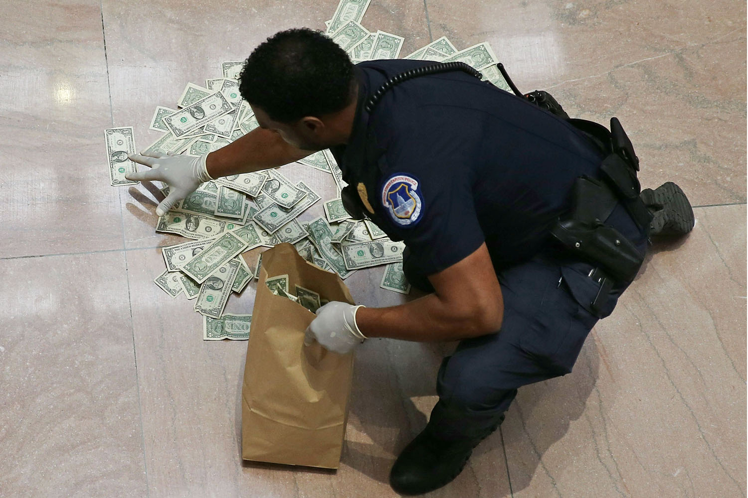 Oct. 9, 2013.  A U.S. Capitol Police officer picks up money that was thrown on the floor by activists protesting against the government shutdown at the Hart Senate Office building, in Washington, DC.