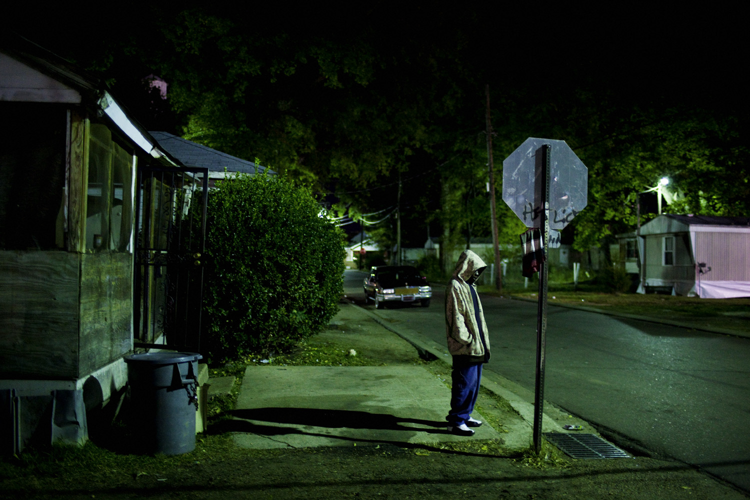 A young man lit only by the dim glow of street lights stands on the corner of Young and Pelican late at night in the Baptist Town neighborhood of Greenwood, Mississippi. Nov. 4, 2010.