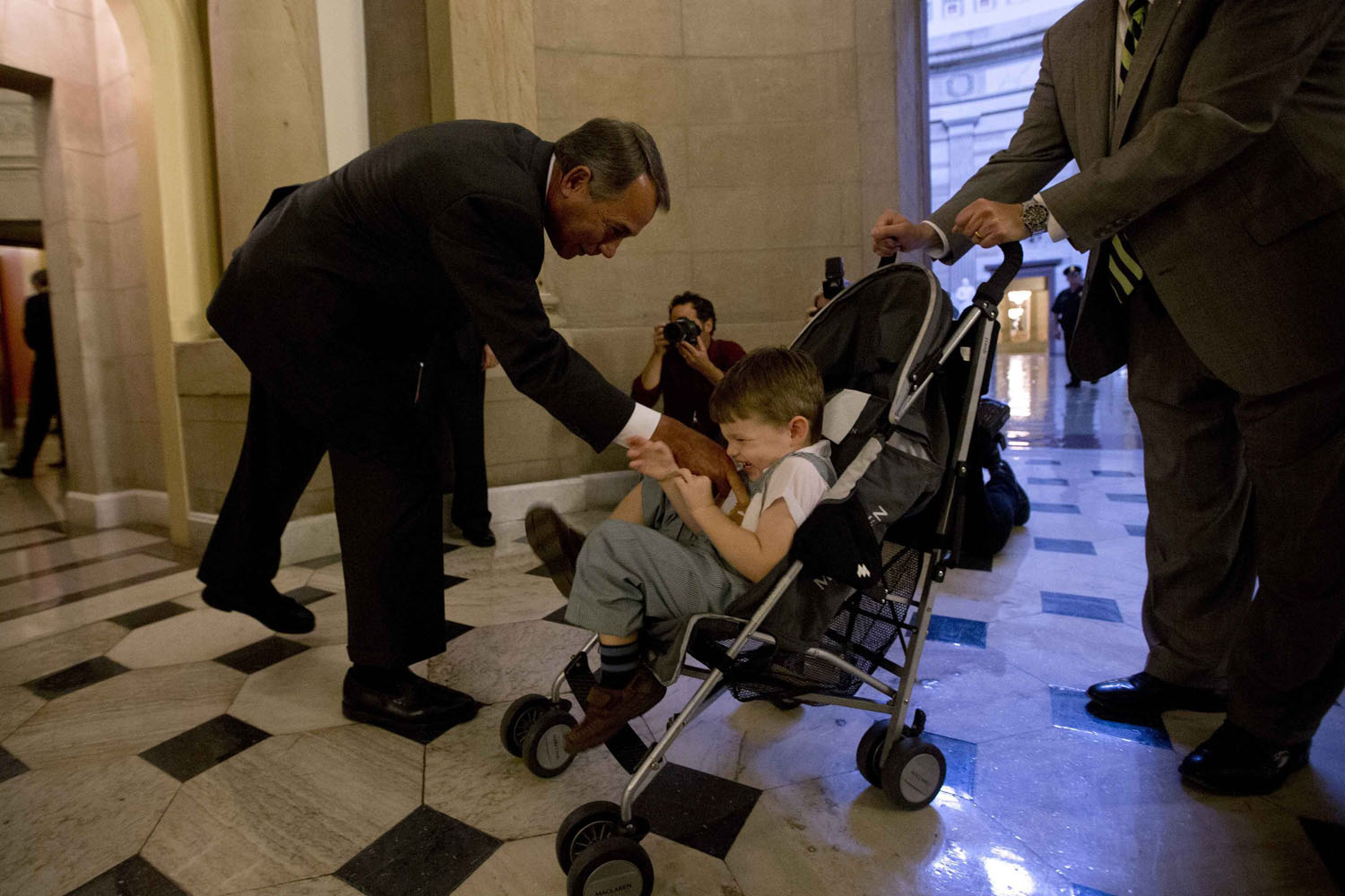 Oct. 10, 2013. U.S. House Speaker John Boehner (R-OH) (L) tickles John Griffin III, son of U.S. Rep. Tim Griffin (R-AR) (R), after a house vote on border safety and security in Washington.