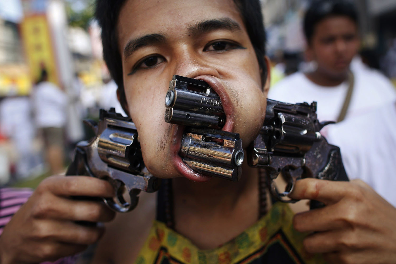 Oct. 11, 2013. A devotee of the Chinese Jui Tui Shrine, with two guns pierced through his cheeks, takes part in a street procession during the annual vegetarian festival in Phuket, Thailand.