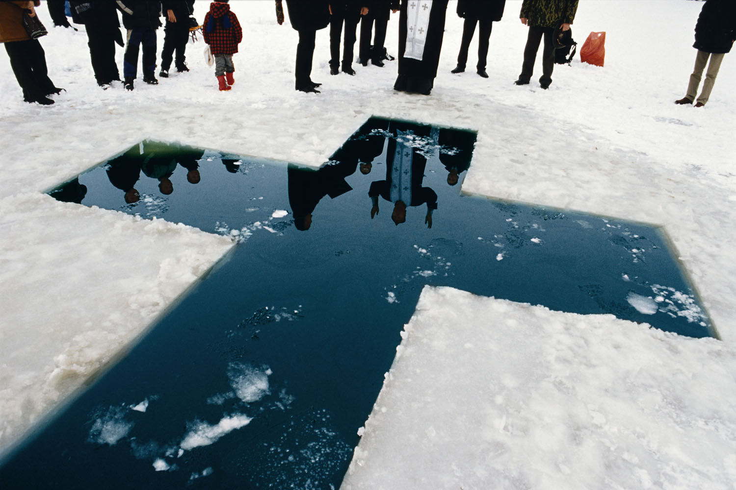 The population of Transdniester is mainly ethnic Russians and the main religion is Russian Orthodox Christianity. Here, a priest gives his blessings before a christening in the icy waters of January. Transdniester, Maldova. 2004.                                                                                             (WPP 2nd prize, Daily Life stories, 2004)
