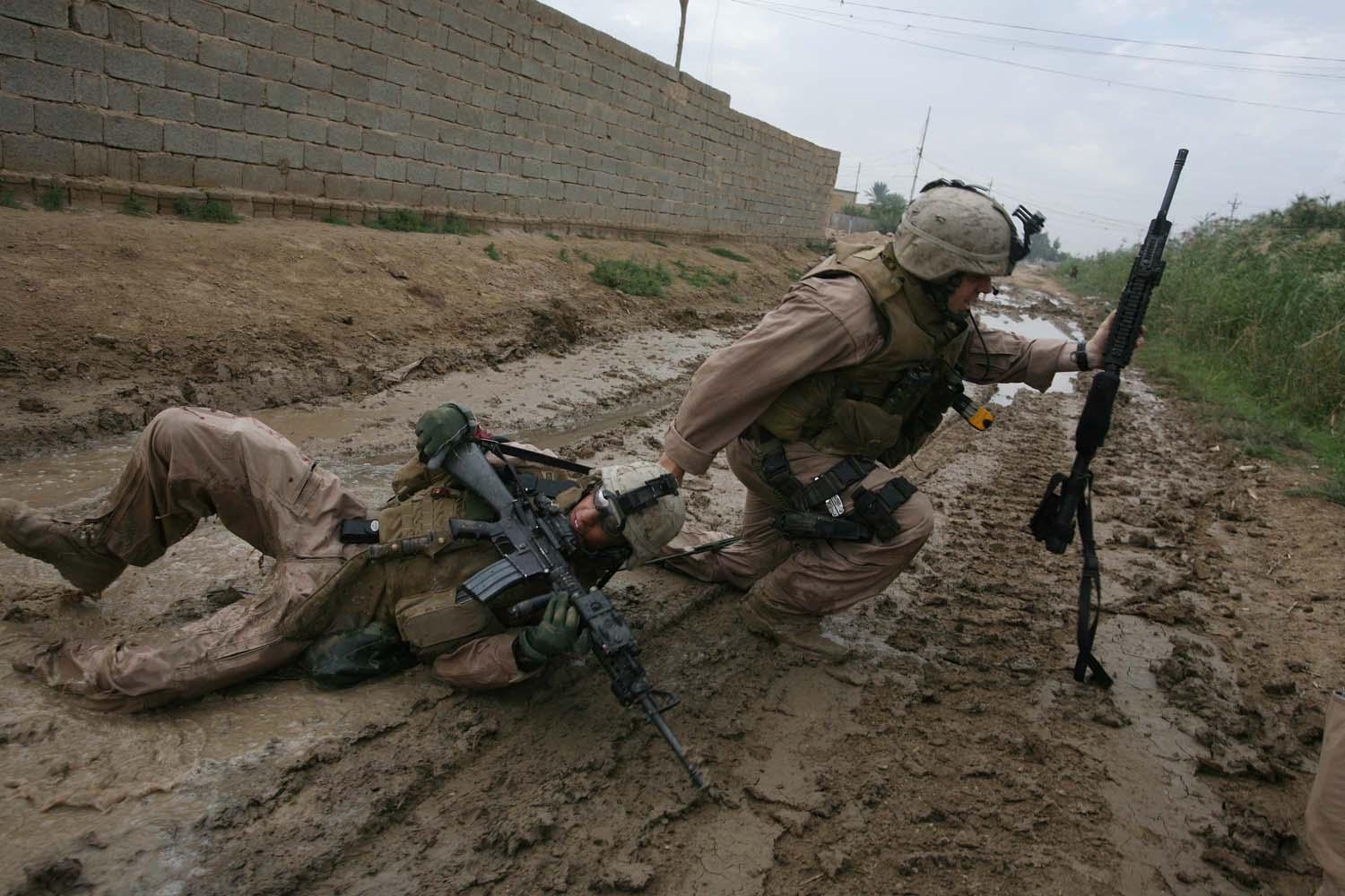 Sgt Jesse E. Leach drags Lance CPL Juan Valdez of the for 4th mobile assault platoon Weapons company 2nd battalion 8th Marines to safety moments after he was shot by a sniper during a joined patrol with the Iraqi Army in Karmah, Anbar Province, Iraq. Valdez was shot through the arm and the right side but survuved. Oct. 31, 2006.                                                              (WPP Honorable mention, Spot News Stories, 2006)