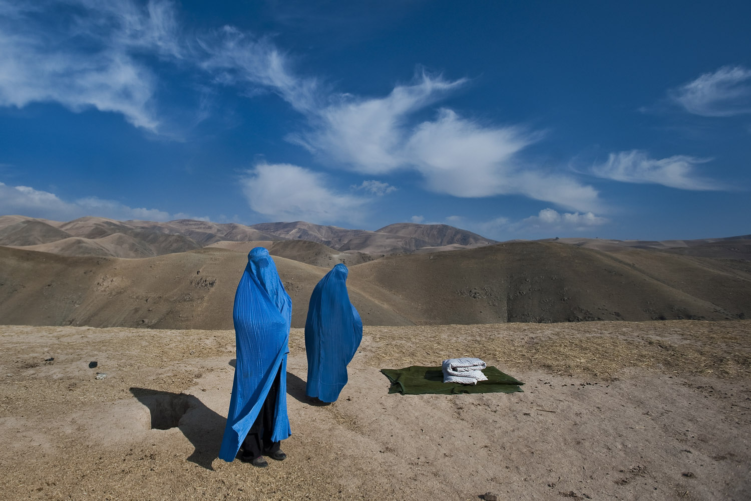 Noor Nisa, 20, pregnant, and her mother, Nazer Begam, 40, who live in Weha village, a four hour drive by car to the clinic in Faizabad, wait along the side of the road to be transported to the hospital, after their car broke down, in Badakhshan province, Afghanistan. Nov. 14, 2009. Nisa's water had just broken. Her husband, Shir Mohammad, who had lost two wives and whose first wife had died during childbirth, was determined to get Nisa to the hospital but his borrowed car broke down, so he went to find another vehicle. Nisa, her mother and her husband were eventually taken by the photographer and her interpreter, who happened to be driving by, to the hospital where Nisa delivered a baby girl.