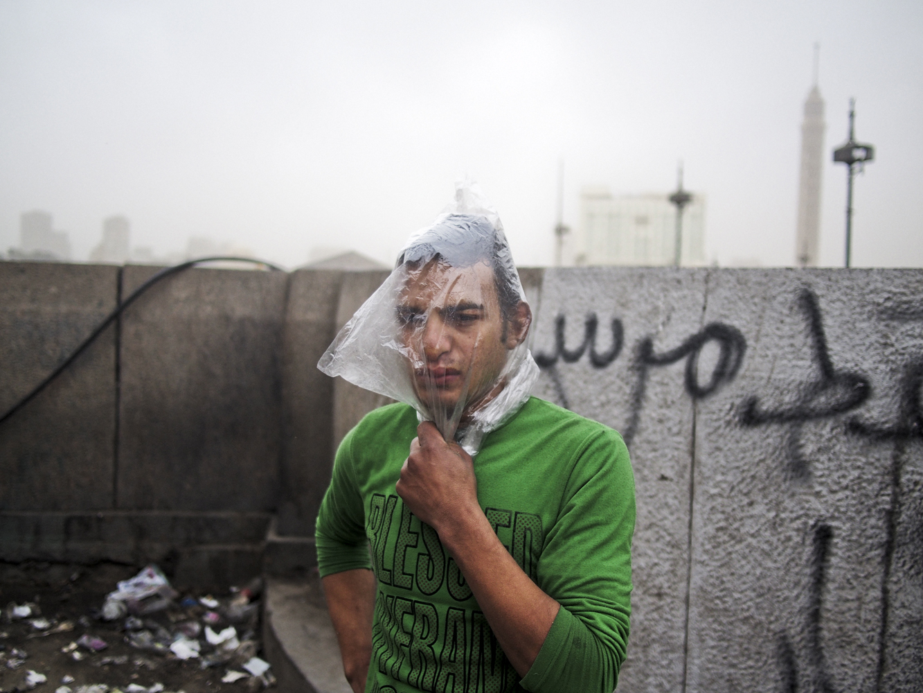 A protestor covers his head with a plastic bag as a makeshift gas mask during clashes near Tahrir Square in Cairo.  January 28, 2013.