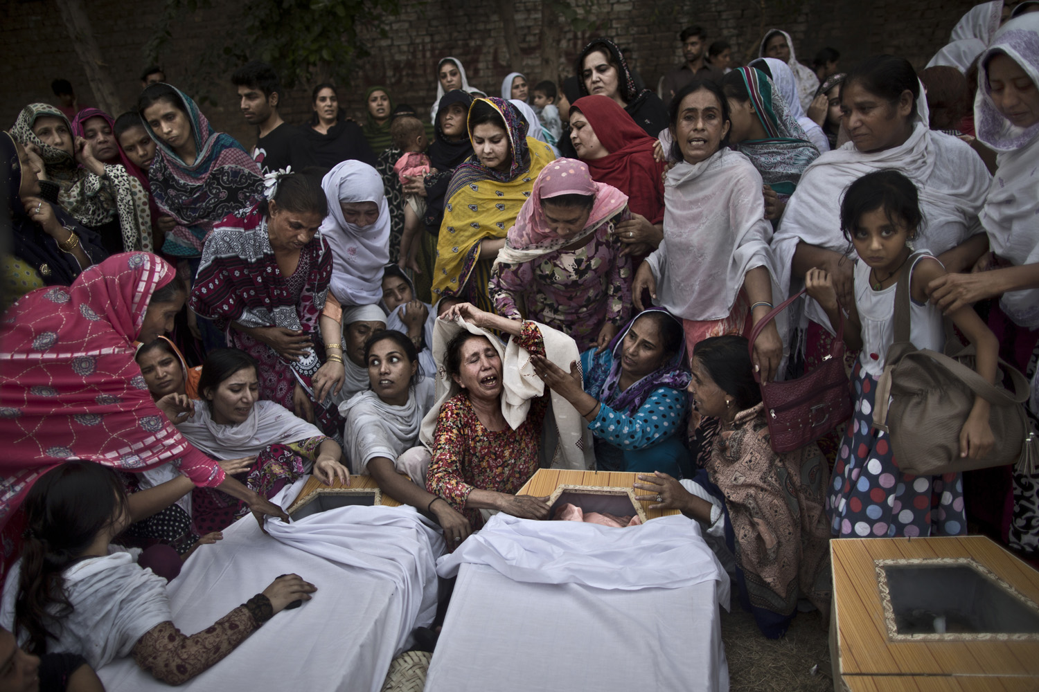 Pakistani women grieve over the coffins of their relatives, who were killed in a suicide attack on a church, in Peshawar, Pakistan. Sept. 22, 2013.
