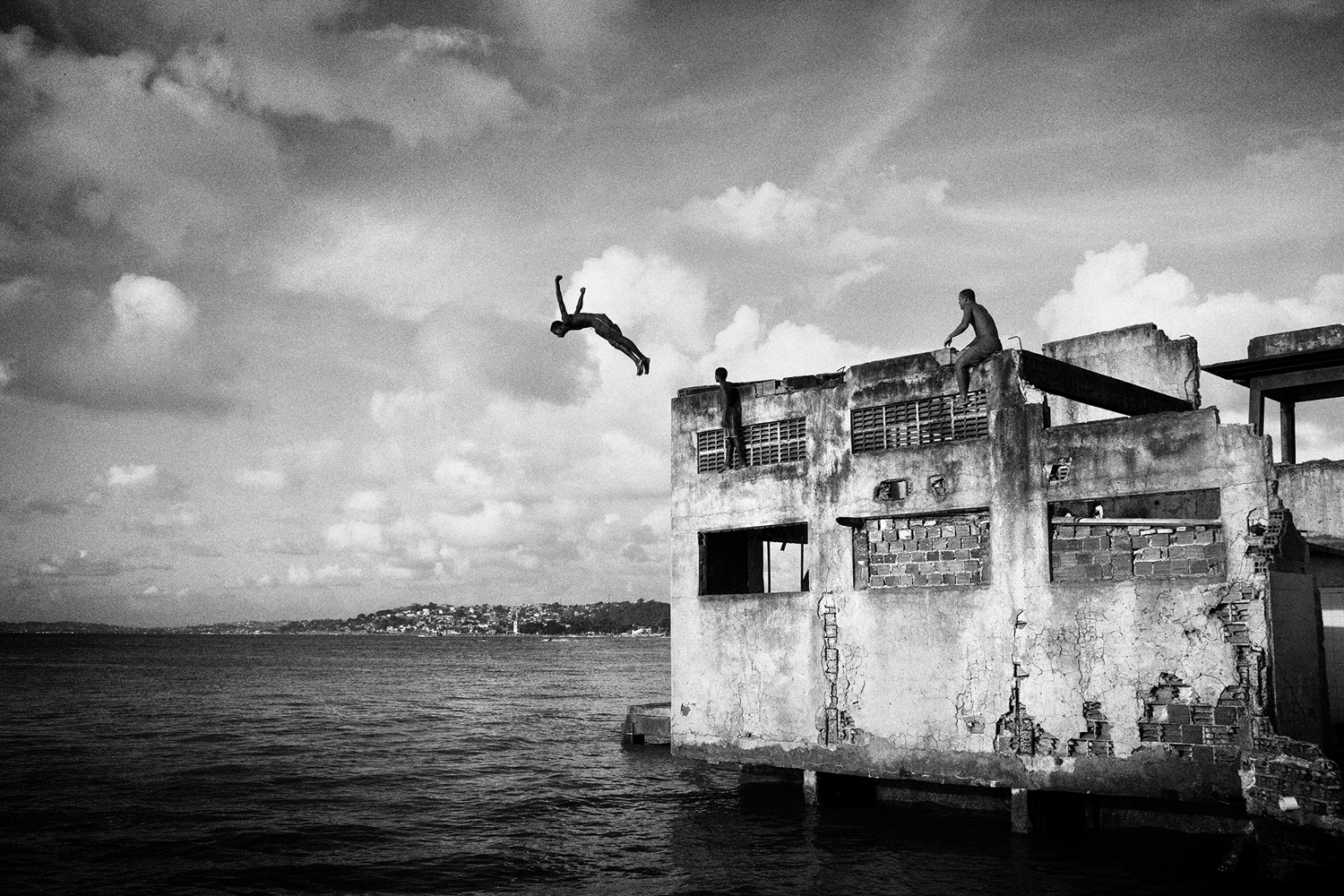 A boy jumping from a building of an abandoned chocolate factory, Salvador de Bahia, Brazil. March 20, 2011.