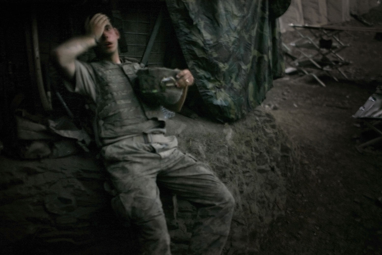 A soldier from 2nd platoon rests at the end of a day of heavy fighting at the 'Restrepo' outpost. The position was named after the medic Juan Restrepo from 2nd Platoon who was killed by insurgents in July 2007. Korengal Valley, Afghanistan. 2007.                                                                                             (WPP 1st prize, Photo of the Year, 2007)